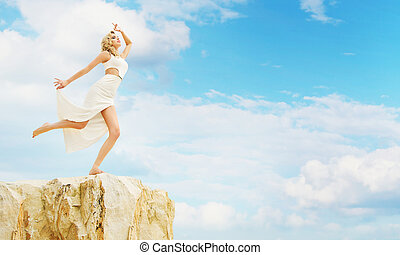 Blond woman trying to jump off the rock - Blond lady trying...