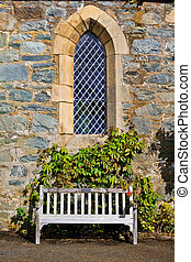 Solitary bench - White bench below an antique window with...