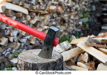 Axe and fire wood - Axe thrust in a birch chock against...