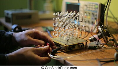 Cube of LEDs, a scientist connects the supply and the cube...