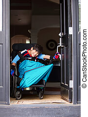 Disabled boy in wheelchair opening front door - Smiling...