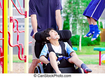 Disabled boy in wheelchair enjoying watching friends play at...