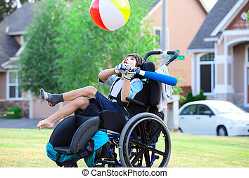 Disabled boy hitting ball with bat at park - Disabled little...