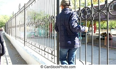 Rear  view of a boy walking on metal fence