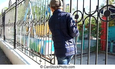 Portrait of a small boy playing on the school fence