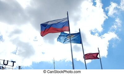 Russian flag waving in the wind over blue sky.