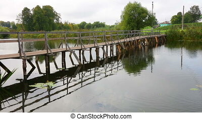 wooden bridge through the small river in summer day
