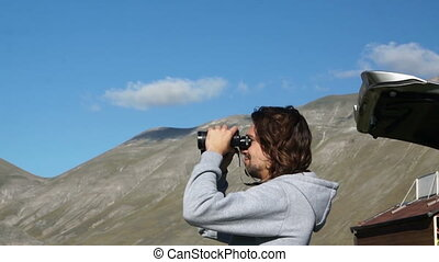 Young guy in sweater with hood looking through binoculars