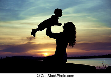 Woman lifting up her child - Woman lifting up her little...