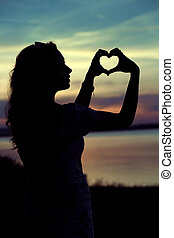 Womans silhouette making the heart gesture - Womans...