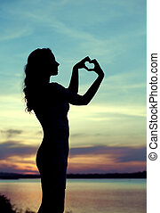 Silhouette of the woman making the heart sign - Silhouette...