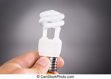 Hand holding energy efficient light bulb over dark...