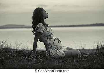 Adorable pregnant woman lying on the grass