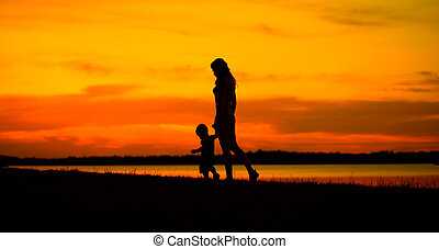 Mother with baby looking at the beautiful sunset