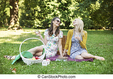 Two cheerful girlfriends enjoying the spare time in park -...