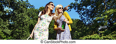 Two laughing women sightseeing a park