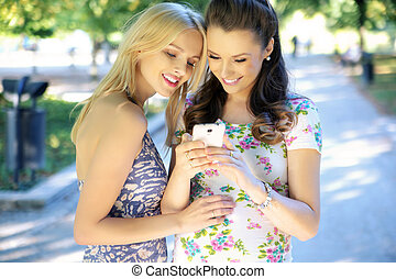 Two women texting their girlfriend - Two young women texting...