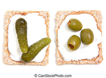 Canapes with gherkins and olives on a white background seen...