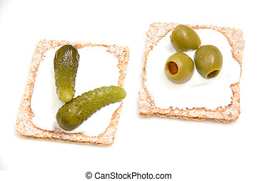 Canapes with gherkins and olives on white background