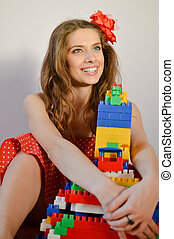 portrait of beautiful funny young pinup girl with great dental whitening teeth smile in red polka dot dress having fun playing with toy constructor and looking up on light copy space background