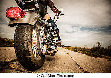 Biker girl riding on a motorcycle. Bottom view of the legs...