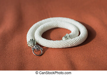 White necklace from beads on a textile background