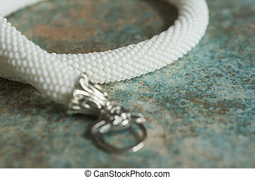 Necklace from small white beads on a textile background