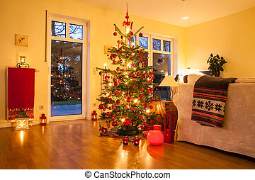 Illuminated Christmas tree in German home with candlelights