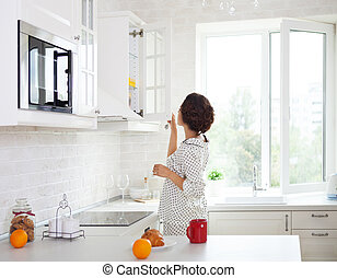 Woman preparing a cup of coffee in her kitchen wearing pajamas