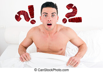 shocked half naked young man in bed looking down at his...