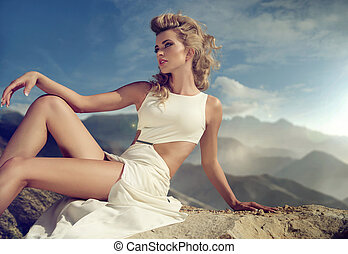 Curly haired woman sitting on the rock
