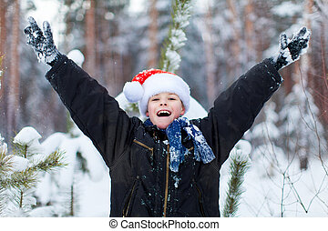 Happy boy in a cap of Santa Claus in the winter forest.