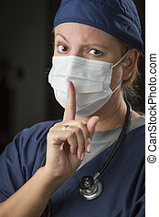 Secretive Female Doctor with Finger in Front of Mouth -...