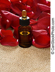 Products rose oil - Red rose petals and massage oil on...