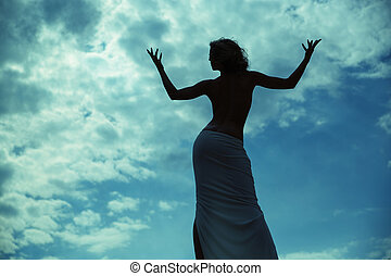 Half-naked woman posing over the blue sky