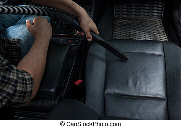 Vacuuming the car - Young man vacuuming grey armchair in his...