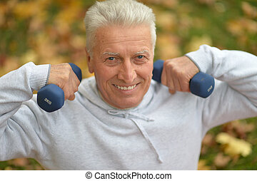 Elderly man exercising with dumbbells in autumn park