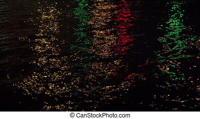 Reflections of coloured lights in the night the river. 4K. -...