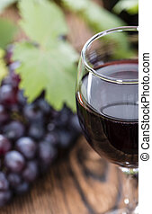 Red Wine with fresh Grapes on wooden background
