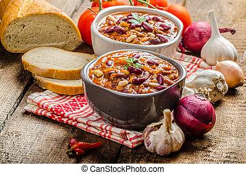 Homemade chilli con carne, bio bread and piri piri peppers
