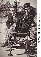 Fashion couple sitting on bench in vintage style and woman...