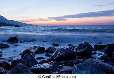 Sea landscape with stones and waves before sunrise