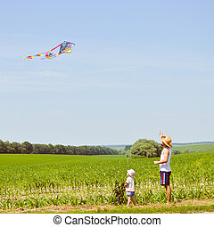 happy family moments: image of father & son having fun playing with kite outdoors on summer sunny day, green field & blue sky outdoors copy space background