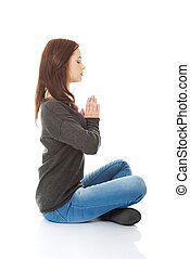 Pretty student girl meditating in lotus pose She is relaxed...