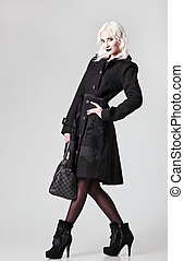 Studio fashion shot: a beautiful girl in black coat and...