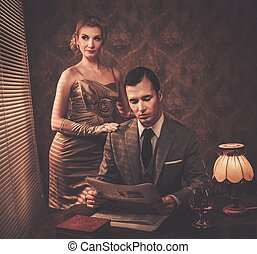 Man in suit reading newspaper with woman behind him