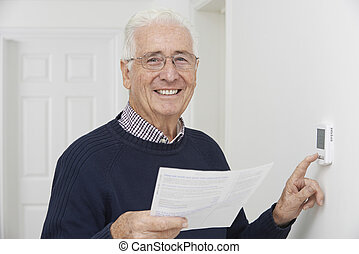 Smiling Senior Man With Bill Adjusting Central Heating...