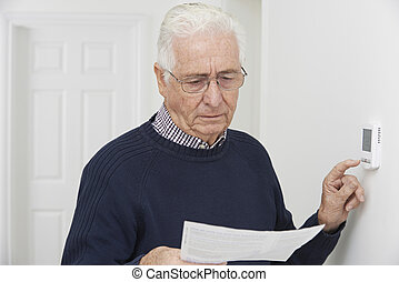 Worried Senior Man With Bill Turning Down Central Heating...