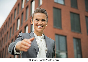 Portrait of happy business woman stretching hand for...