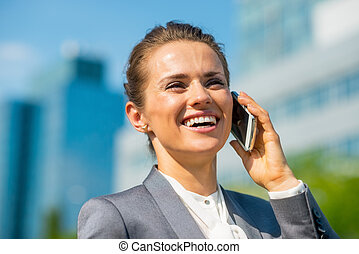 Portrait of happy business woman talking mobile phone in...